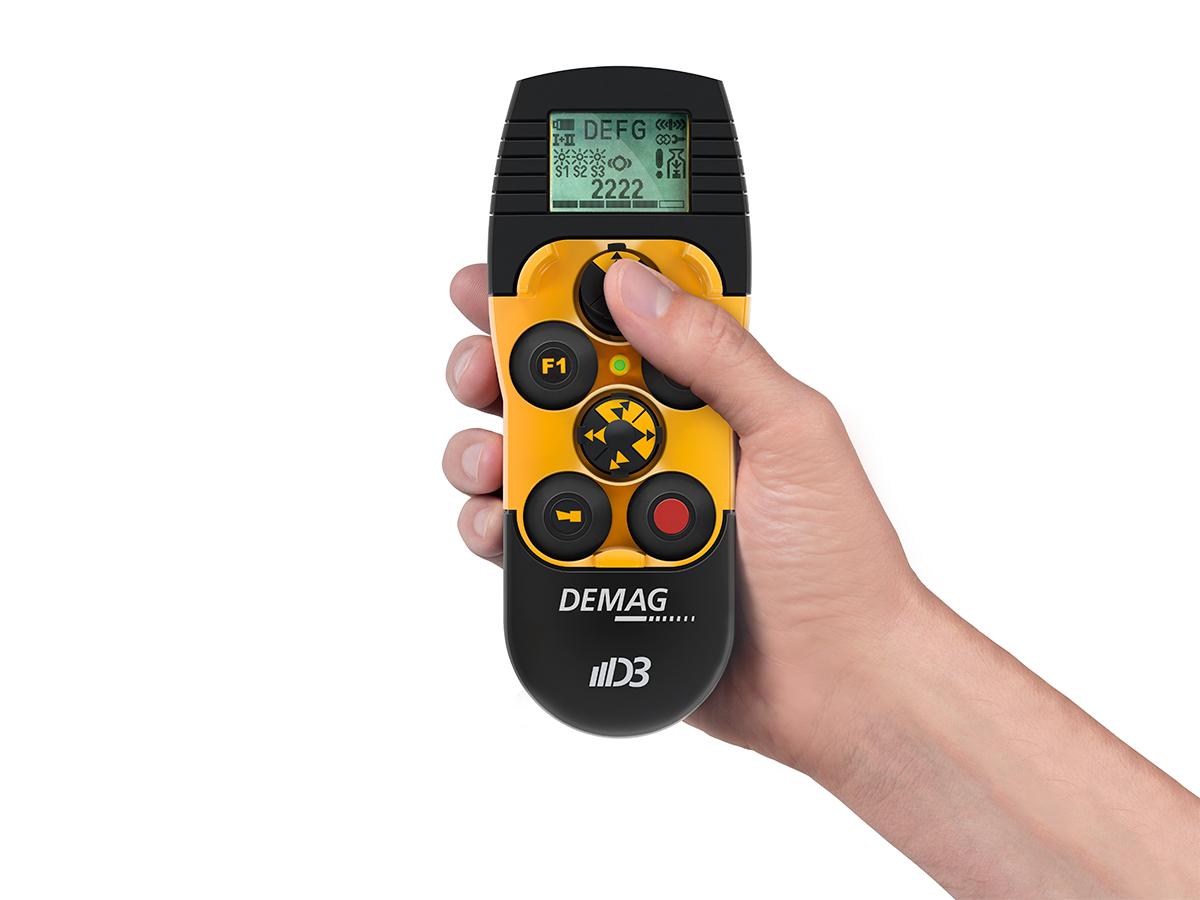 Hand som holder DRC-DC styringsapparat fra Demag. Produktfoto.