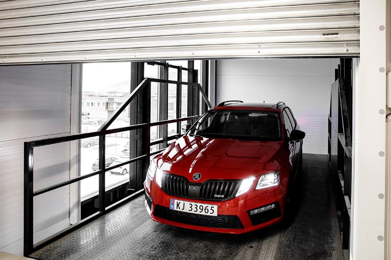 Rød bil parkert i bilheis. Foto.