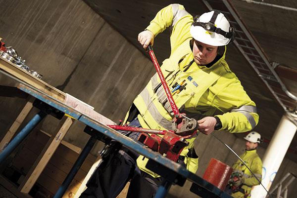 Arbeidskar holder rørverktøy i hånda
