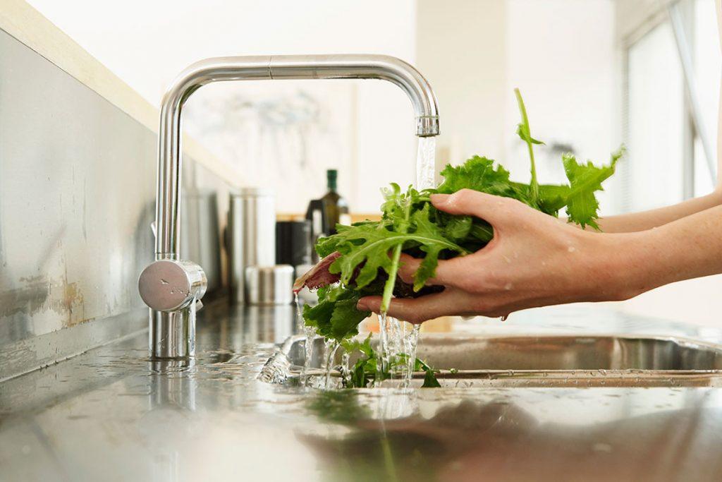 Kjøkkenkran med rennende vann over grønnsaker