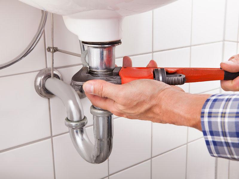 rørlegger skrur under vasken på badet.