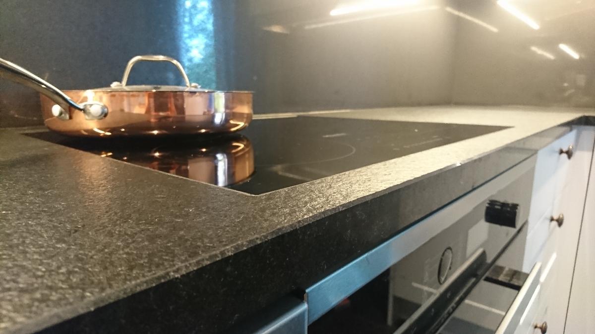 Bilde av induksjonstopp, planlimt i sort børstet granitt